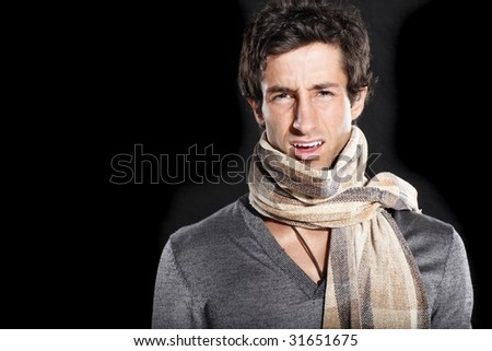 Frustrated man wearing fashionable scarf and sweater - stock photo
