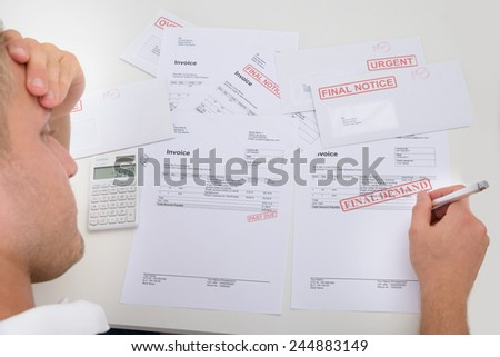 Frustrated Man With Unpaid Bills And Invoices - stock photo