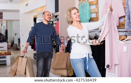 Frustrated mature husband tired awaiting his wife shopping in clothing store