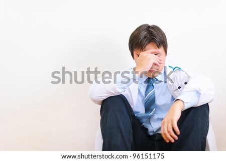 Frustrated medical doctor sitting on floor - stock photo
