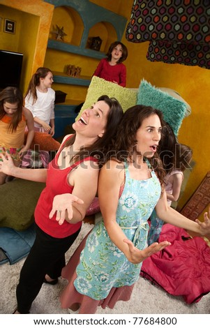 Frustrated mom and babysitter among misbehaving little girls at a sleepover - stock photo