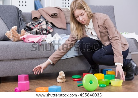 Frustrated mother in office clothes cleaning up the flat from scattered toys and children's stuff - stock photo