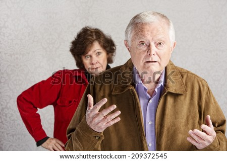 Frustrated older man with hands up and annoyed woman - stock photo