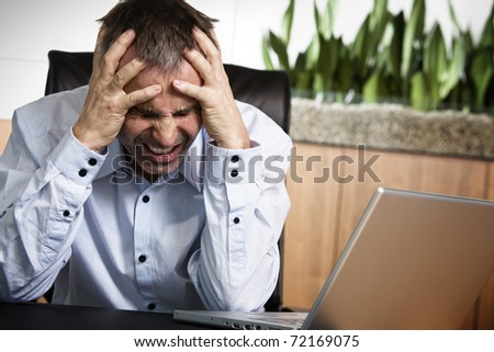 Frustrated overloaded senior businessman being furious about work and clinching his teeth, sitting at office desk in front of laptop.