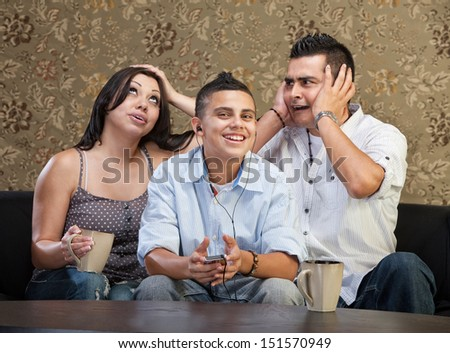 Frustrated parents with teenager plugged in to mp3 player - stock photo