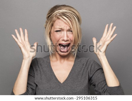 frustrated 20s blond girl crying, losing temper, screaming loud with hands up - stock photo