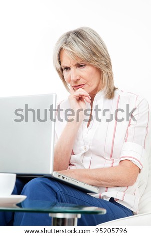 Frustrated senior woman with laptop at home on couch - stock photo