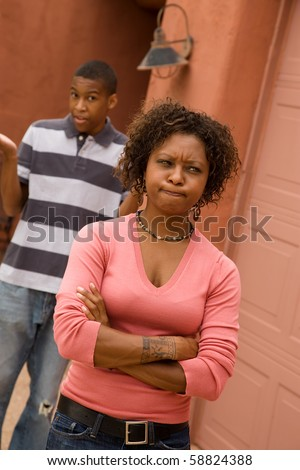 Frustrated single-mom and son outdoors in front of house - stock photo
