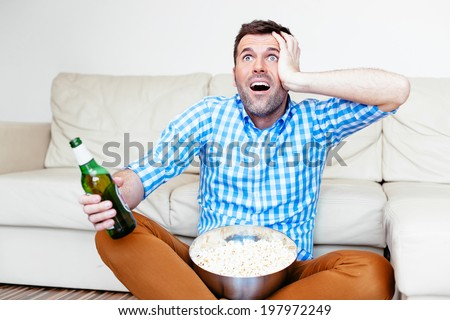 Frustrated sports fan shocked at his team's performance on tv - stock photo
