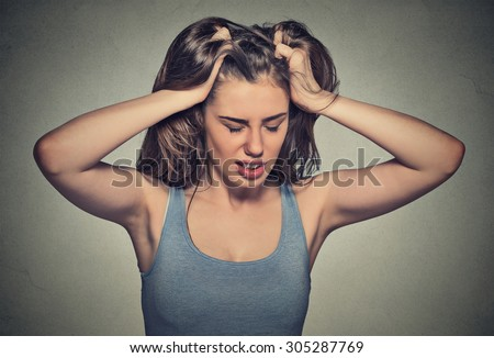 Frustrated stressed young woman. Headshot unhappy overwhelmed girl having headache bad day pulling her hair out isolated on grey wall background. Negative emotion face expression feelings perception - stock photo