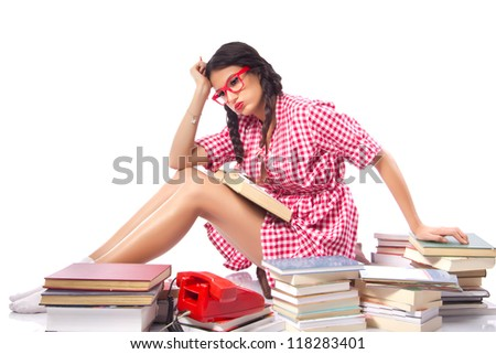Frustrated Student with books - Attractive female student sitting behind a large pile of books with a stressed and burnt out look on her face. Red vintage dress, large nerdy glasses, white background - stock photo
