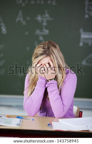 Frustrated teenage female student with covering face with hands at desk in classroom - stock photo