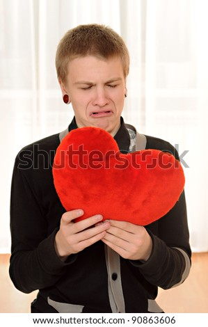 frustrated teenager  with a teddy heart in hand - stock photo