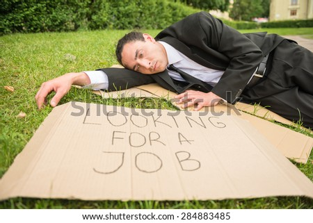Frustrated unemployed man with sign lying down the lawn. - stock photo
