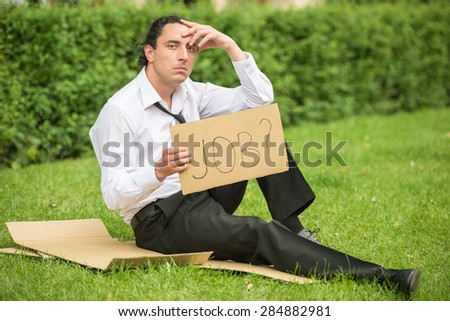 Frustrated unemployed man with sign sitting at the lawn. Depression. - stock photo