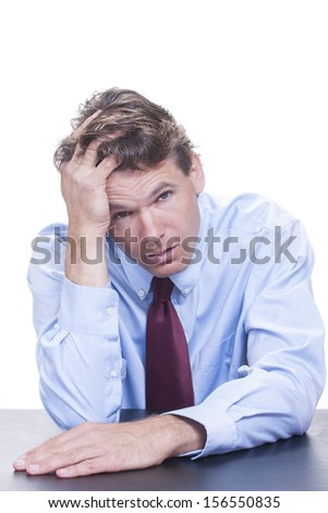Frustrated white male office worker leans his head into his hand as he slouches at his desk fully exhausted and defeated on white background