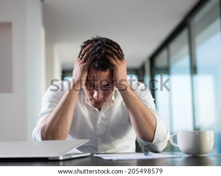 frustrated with problems young business man working on laptop computer at home - stock photo