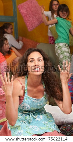 Frustrated woman among wild children with hands in the air - stock photo