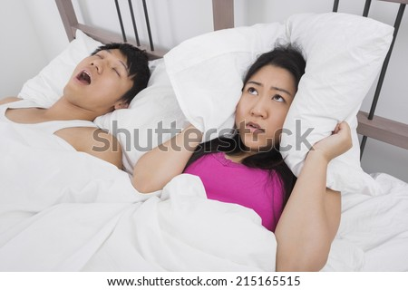 Frustrated woman covering ears with pillow while man snoring in bed - stock photo