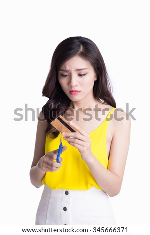 Frustrated woman cutting up her credit card on white background - stock photo