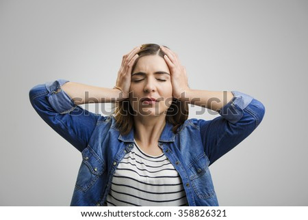 Frustrated woman holding head in hands and expressing pain