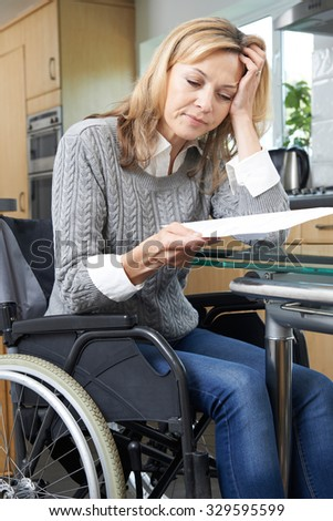 Frustrated Woman In Wheelchair Reading Letter - stock photo