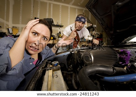 Frustrated woman leaning on car with incompetent male mechanic in background - stock photo