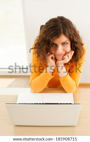 Frustrated woman looking at camera with her laptop on table - stock photo