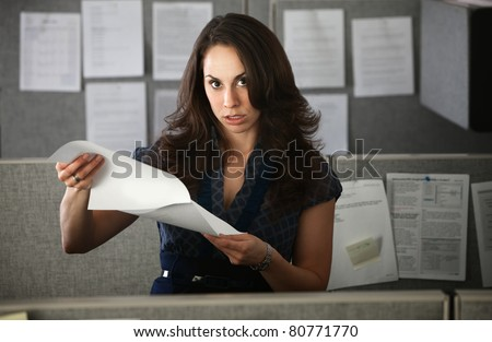 Frustrated woman office worker holding documents stands in cubicle - stock photo
