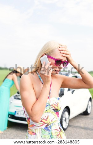 Frustrated woman using cell phone while friend examining broken down car at countryside - stock photo