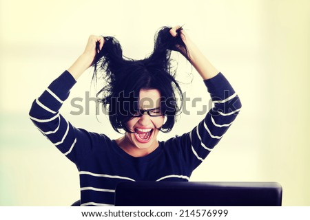 Frustrated woman working on laptop, isolated on white
