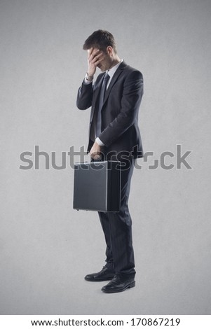 Frustrated young businessman covering his eyes. - stock photo