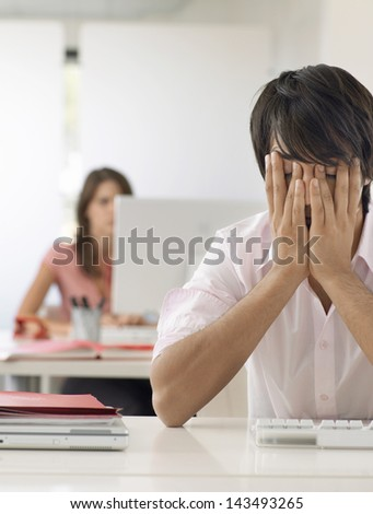 Frustrated young businessman with hands on face at desk with female colleague in background - stock photo