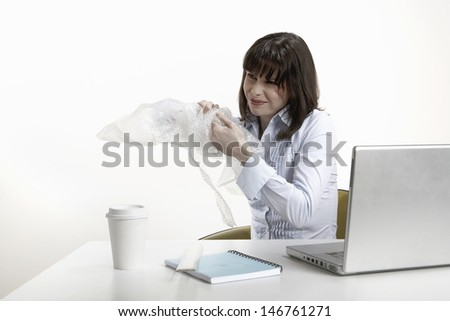 Frustrated young businesswoman playing with plastic bubble wrap at desk - stock photo