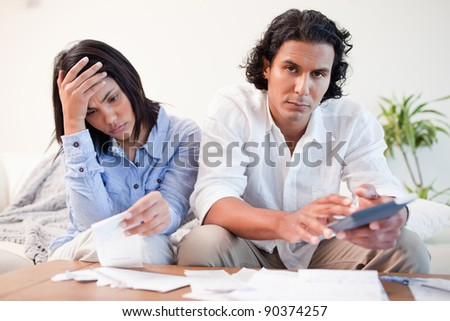 Frustrated young couple checking their bills in the living room - stock photo