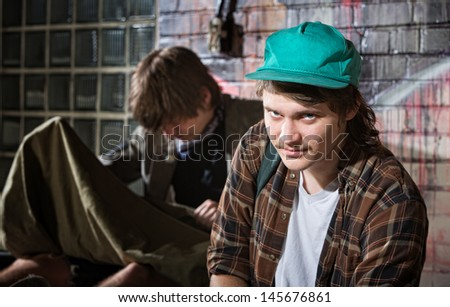 Frustrated young homeless man with friend sitting outside - stock photo