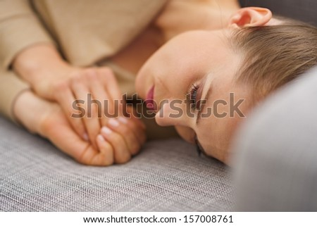 Frustrated young housewife laying on sofa - stock photo