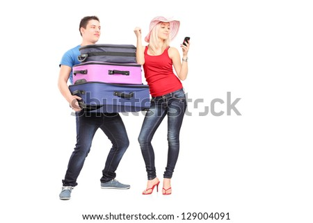 Frustrated young man carrying his girlfriend's baggage while she is making a call - stock photo