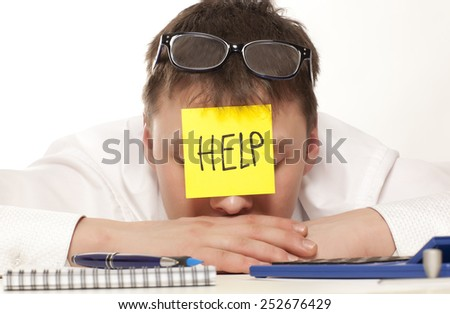 Frustrated young man in formal wear with adhesive note on his forehead leaning his head at the table - stock photo