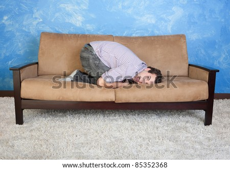 Frustrated young man on sofa - stock photo