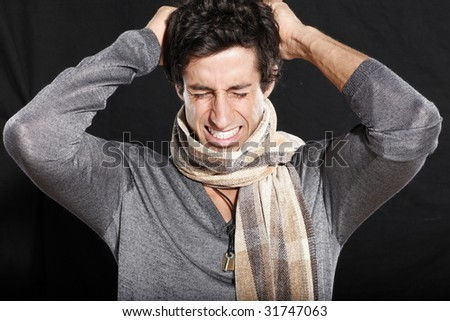 Frustrated Young Man Tearing at Hair - stock photo