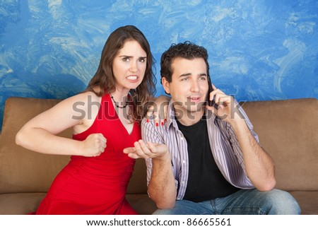 Frustrated young woman gestures to punch man on phone - stock photo