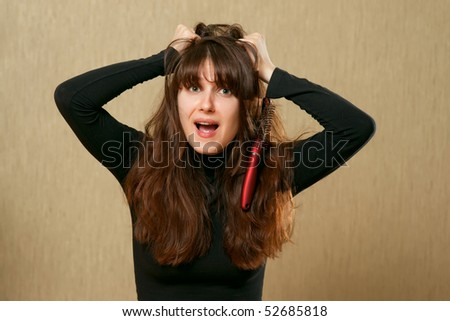 Frustrated young woman having a bad hair day with brush stucks in her hair - stock photo