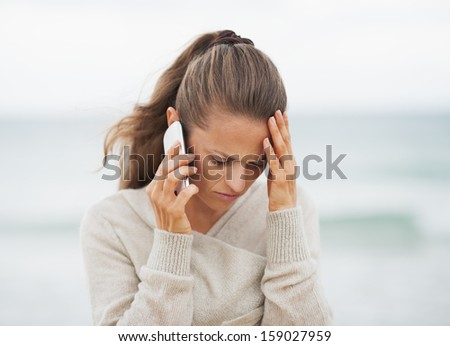 Frustrated young woman in sweater on beach talking cell phone - stock photo