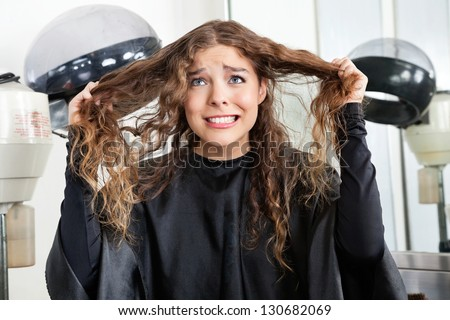 Frustrated young woman pulling her hair in beauty salon