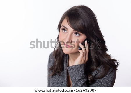 Frustrated young woman talking on a cellphone - stock photo