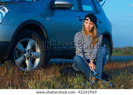 Frustrated young woman with wrench near broken car - stock photo