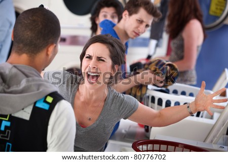 Frustrated young woman yells at a man in the laundromat - stock photo