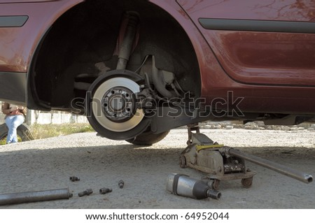 Frustrating young woman reading a book near broken car. Waiting for mobile service team. - stock photo