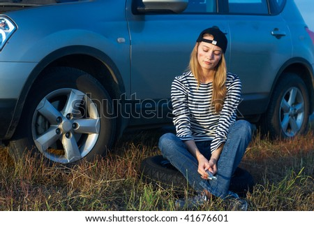 Frustrating young woman with wrench near broken car - stock photo